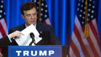 Paul Manafort checks the podium before Republican presidential candidate Donald Trump speaks during an event.