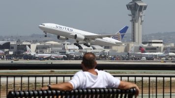 A United Airlines jet takes off near an air traffic control tower at LAX.