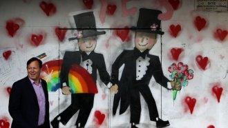 Australian walks past graffiti celebrating same-sex marriage