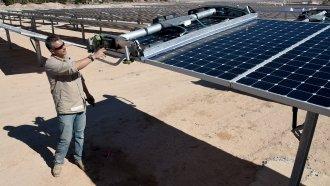 SunPower field supervisor Oscar Madrigal demonstrates using a panel washing robot on a row of solar panels.
