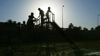 Iraqi children file up the stairs of a slide on a new playground July 2, 2004 in Baghdad, Iraq.