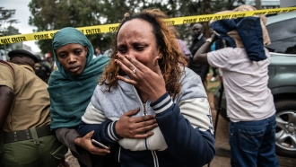 Two women leave the crime scene of the attack on a hotel complex in Kenya
