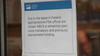 A sign on the door of the USDA office announces the Farm Service Agency is closed.