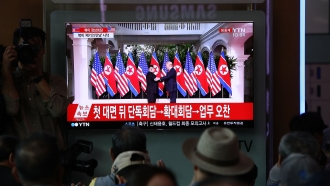 People watch President Trump's meeting with North Korean leader Kim Jong-un on TV