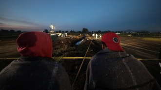 Two residents staring at the damage from the pipeline
