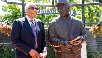 Frank Robinson stands with a statue commemorating his career prior to a Cleveland Indians-Kansas City Royals game.