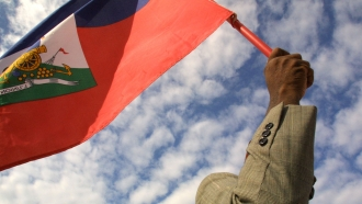 Man holds a Haitian flag in the air