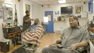 Barbers Telvis Fitzgerald (right) and Lavar Johnson discuss politics inside Presidential Cutz, a barbershop in Richmond, Va.