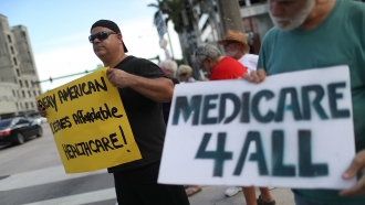 Protesters hold signs supporting Medicare For All