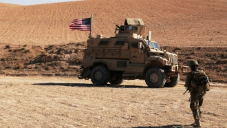 A U.S. soldier walks toward a tactical vehicle in Syria