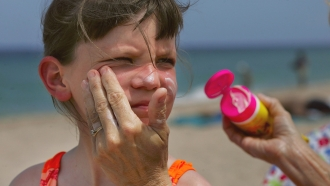 A woman puts sunscreen on a girl's face.
