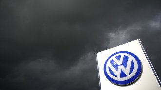 Rain clouds are seen over a Volkswagen symbol at the main entrance gate at Volkswagen production plant.