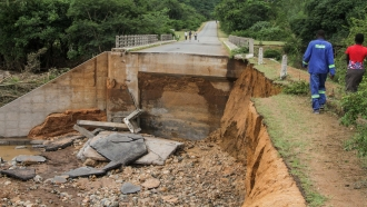 People cross one of several bridges destroyed by Cyclone Idai.