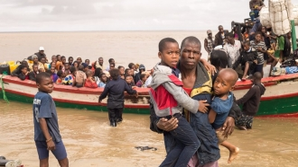 Red Cross volunteers help people off a boat who were rescued after Cyclone Idai.