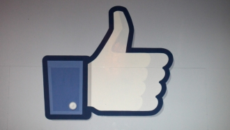 A thumbs up 'like' sign stands at the entrance to Facebook headquarters.