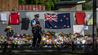 An armed police officer patrols past a New Zealand flag and other tributes near Al Noor mosque