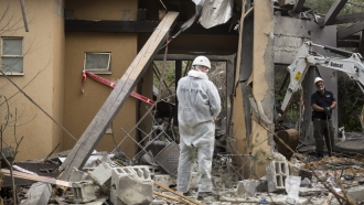 Officials inspect a home in Israel that was bombed early Monday morning.