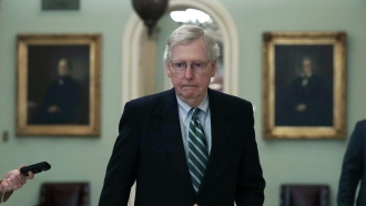 Mitch McConnell walks to a meeting.
