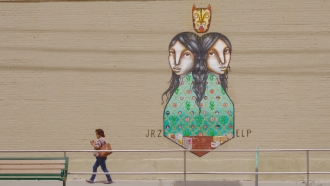 A woman walks by a mural in downtown El Paso.