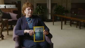 Journalist Laura Parker holds up an issue of National Geographic