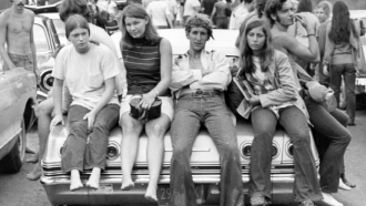 Teens sitting on car during 1969 Woodstock music festival