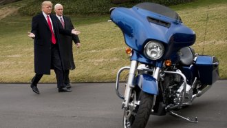 President Donald Trump and Vice President Mike Pence check out a Harley Davidson motorcycle
