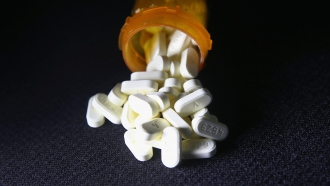 Oxycodone pills spill out of a bottle