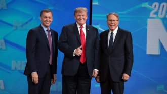 President Trump stands on stage along with NRA executives at the annual NRA Leadership Forum