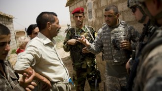 An interpreter speaks with Kurdish villagers during a tri-partite humanitarian mission involving US, Iraqi and Kurdish forces