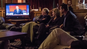 A group of people watch a Fox News nightly report