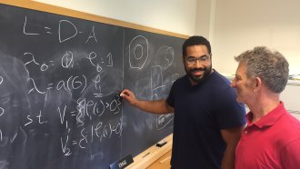 John Urschel writes on a chalkboard