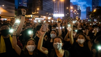Protesters shine lights from their mobile phones during rally against a controversial extradition law proposal on June 16