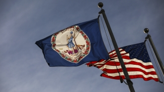 The Virginia State flag and the American flag fly near the Virginia State Capitol, February 9, 2019 in Richmond, Virginia.