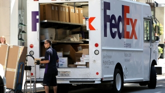 A FedEx worker unloads packages from his delivery truck.