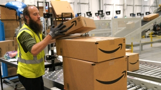 A man stacks Amazon boxes