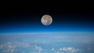 The moon is pictured as the International Space Station orbits above the ocean
