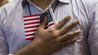 A man holds a U.S. flag to his chest
