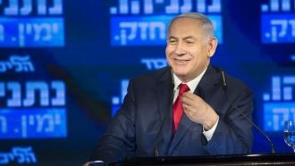 Prime Minister Benjamin Netanyhau smiles behind a podium.