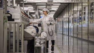 A worker packs up new smartphone devices at the end of the production line at Huawei's production campus