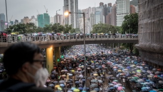 A man watches thousands of anti-government protestors leave a rally in Victoria Park on August 18, 2019 in Hong Kong, China.