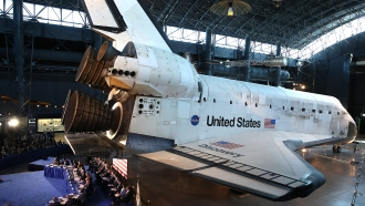 Panel sits on stage in front of a United States space shuttle