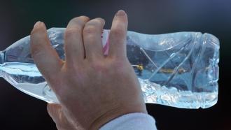 A woman drinks a bottle of water