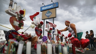 A woman touches a cross at a makeshift memorial for victims outside Walmart.