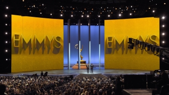 Colin Jost and Michael Che speak onstage at the 70th Emmy Awards