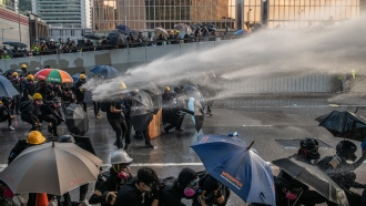 Pro-democracy protesters are hit by a water cannon during clashes at the Central Government Offices on September 15, 2019
