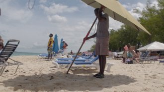 Workers cater to tourists on Nassau's cabbage beach
