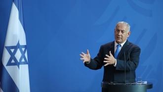 Prime Minister Benjamin Netanyahu stands next to Israel flag