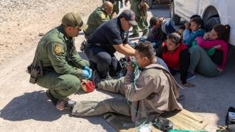 U.S. Border Patrol agents render medical aid to migrants traveling with a group that crossed the border illegally