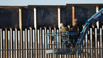 Workers construct part of a barrier along the U.S.-Mexico border