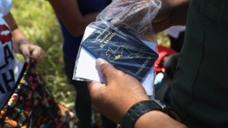 A U.S. Border Patrol agent inspects a Salvadoran passport